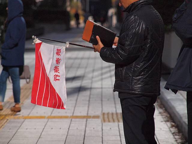 読売旅行の旗を持つ添乗員