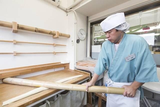 竹を使いテコの原理で麺を打って平たくしてゆく