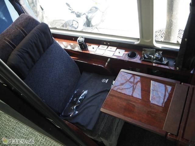 シートの前には折りたたみ式のテーブル、横には電動リクライニング等のスイッチが