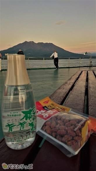 寄港する島の酒とつまみで、夕暮れの桜島を見ながら食前の一杯。