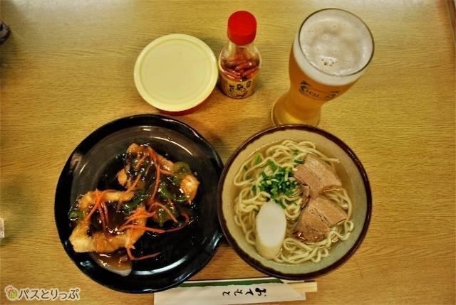沖縄の地ビール「ゴーヤビール」、アオブダイのあんかけ、ソーキそば。ソーキそばは、お好みでコーレーグス(島唐辛子を泡盛に漬け込んだ沖縄の調味料)やしょうがを添えて。