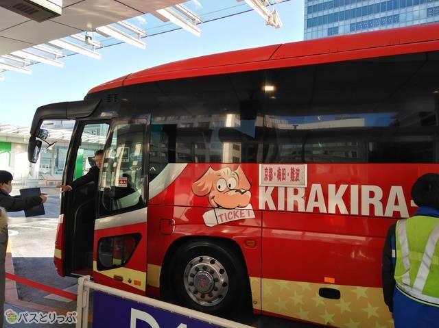 赤色の車体にキャラクターやキラキラの星が描かれた、個性的なデザインのバス