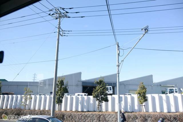 いすゞの工場のノコギリ屋根が車窓に映る