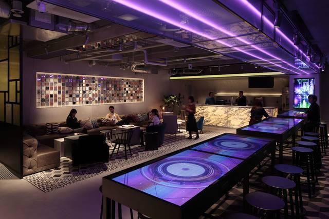 4階ラウンジ。手前のテーブルにはサイバーテイストの映像が流れて非日常的な空間に(画像提供:グローバルエージェンツ)