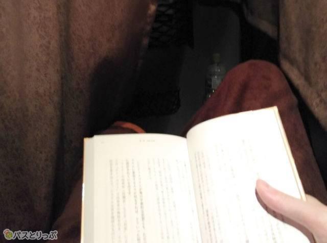 読書灯のあかりで本を読む