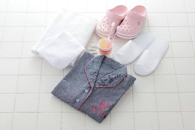 部屋備え付けのタオル、歯ブラシ、ナイトウェア、スリッパ。可愛いピンクのクロックスも