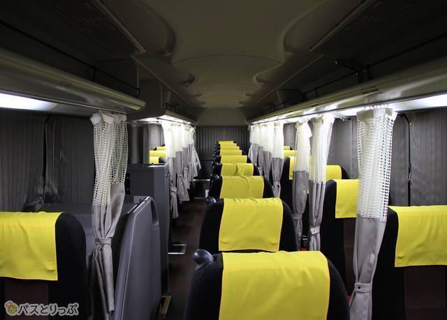 座り心地が良いシートが並ぶ車内。橙色のヘッドカバーがワンポイントの華を添えている