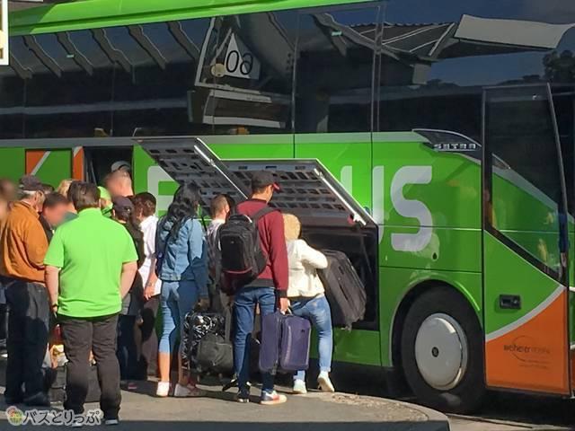 トランクに荷物を預ける乗客