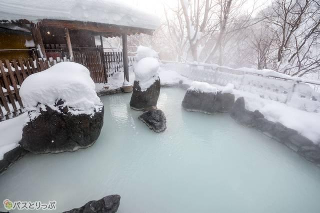 天然の大きな石を配した露天風呂。内風呂に比べて白に近くにごった湯