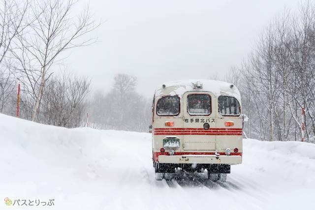 雪道を帰っていくバスを見送る