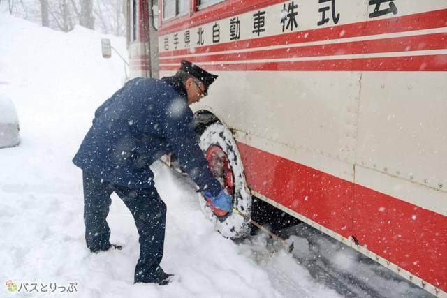 雪降りしきる中、車体にできたつららを叩き落とす古川さん