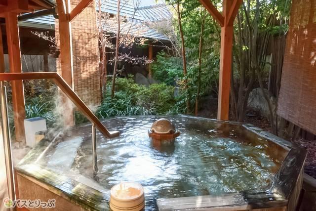 湯気立ち上る温泉で体を温める