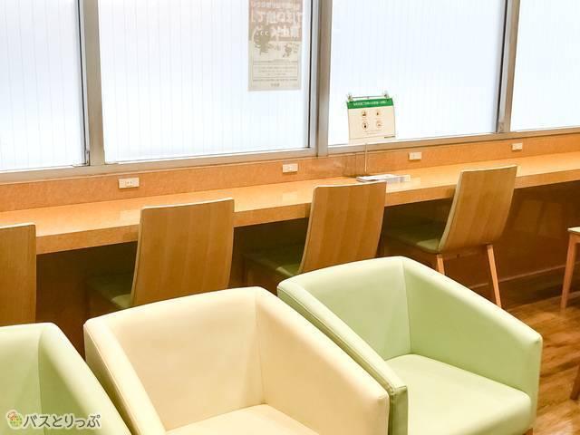 ソファやコンセント付きのテーブルが用意された待合室