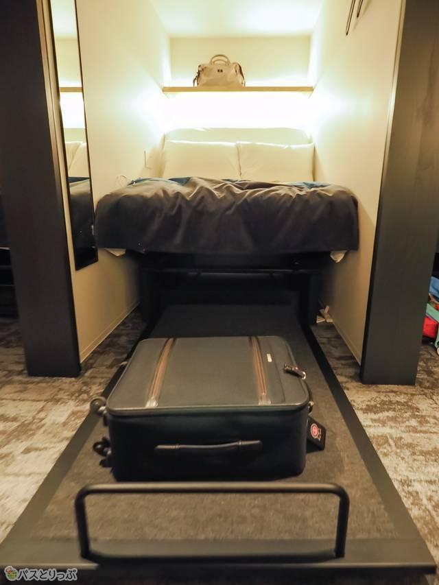 ベッド下の取っ手を引っ張ると荷物置きスペースが現れる。上の棚も細かな荷物を置くのに便利