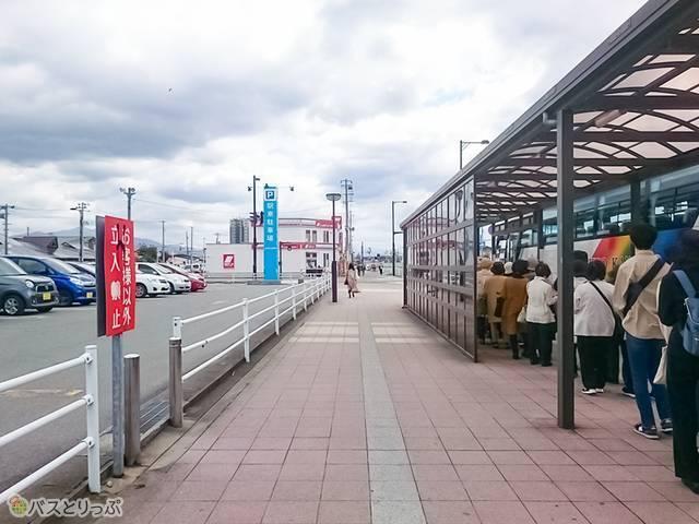 右手が4番乗り場、左手の赤い看板のところを抜けると「秋田駅東駐車場内バス停」